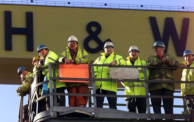 Harland and Wolff shipyard workers look on as the Anvil Point, the last ship to be built at the Belfast shipyard, is named in a ceremony on January 17, 2003, in Belfast, Northern Ireland.