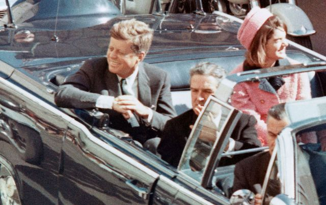 President John F Kennedy and his wife Jackie greeting the crowds from their motorcade on that fateful day in Dallas.