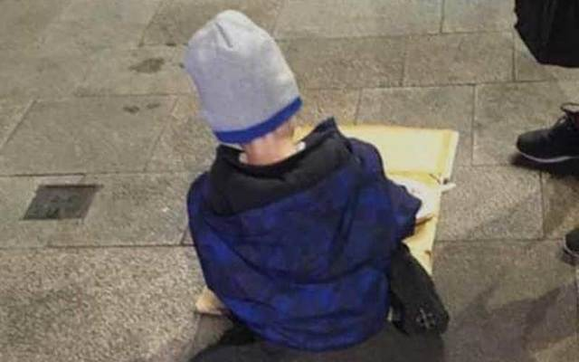 """This photo of a homeless five-year-old Irish boy, \""""Sam,\"""" eating his dinner off a piece of cardboard in Dublin has sparked outrage."""