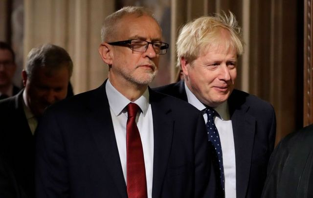 Britain\'s Prime Minister Boris Johnson (R) and opposition Labour Party Leader Jeremy Corbyn walk through the Commons Members Lobby during the State Opening of Parliament at the Palace of Westminster on October 14, 2019, in London, England.