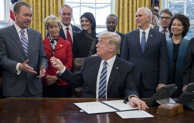 President Donald Trump hands his pen to Mick Mulvaney beside members of his cabinet, including Vice President Mike Pence, in the Oval Office of the White House on March 17, 2017.