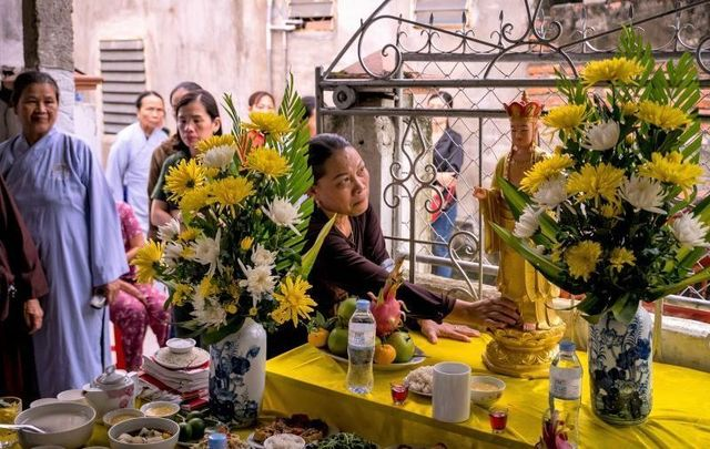 Family members and neighbors of Pham Thi Tra My, who has since been identified as one of the victims, attend a praying ceremony with Buddhist monks in front of a makeshift shrine her house on October 28, 2019 in Ha Tinh province, Vietnam.