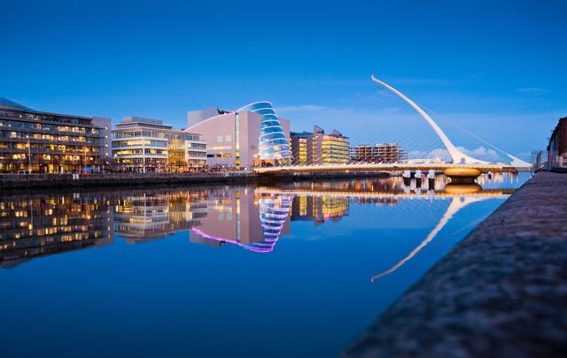 Samuel Beckett Bridge and Convention Center and surrounding buildings on a blue evening with buildings reflected in River Liffey.\n