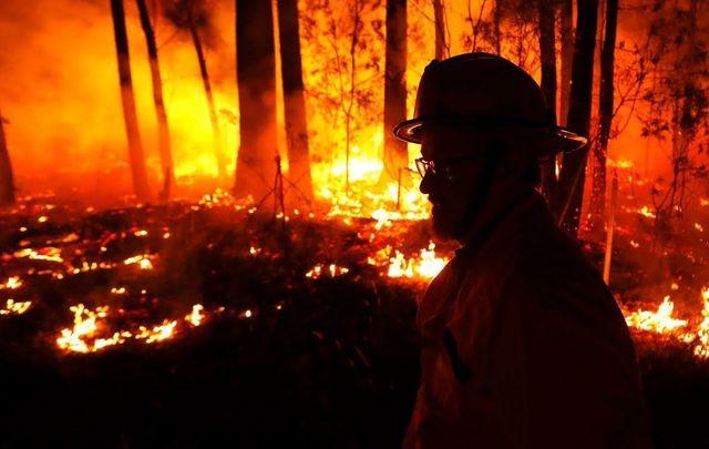 A firefighter battles flames in Australia.