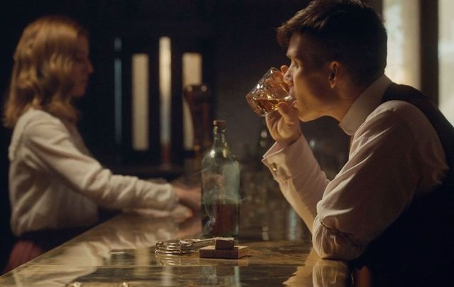 Cillian Murphy, as Tommy Shelby, drinking Irish whiskey in Peaky Blinders.