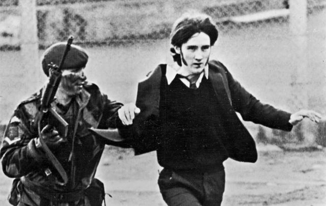 """January 30, 1972: A British paratrooper takes a captured youth from the crowd on \""""Bloody Sunday,\"""" when British paratroopers opened fire on a civil rights march in Derry."""