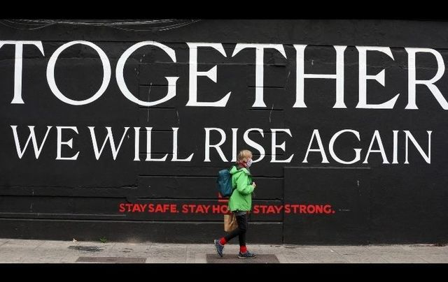 "October 19, 2020: A person wearing face masks passes by a mural saying ""Together we will rise again\"" on Chancery Street in Dublin."