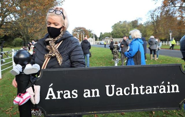 October 26, 2020: Protesters tie baby shoes to a gate during a Mother and Baby Home protest event at Aras an Uachtarain gate in Dublin.