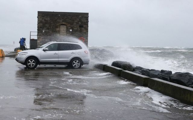 A car is showered in sea spray as Storm Brendan hits in January.