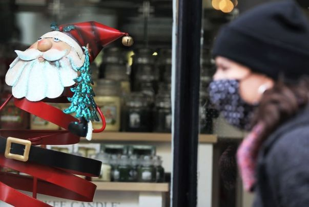 November 4, 2020: A person wearing a face mask passes a Christmas display in a shop window in St Stephen\'s Green shopping center.