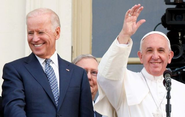 September 24, 2015: Vice President Joe Biden stands beside Pope Francis, who waves to the crowd from the balcony of the US Capitol building, after the first-ever papal address to a joint meeting of the US Congress.