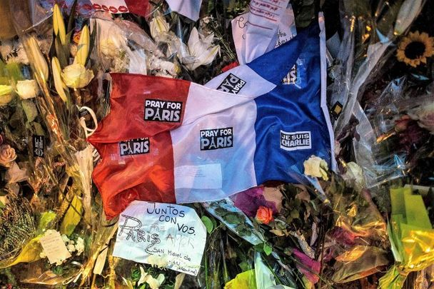 November 16, 2015: A French flag lays on flowers in memory of the victims of Friday\'s attack in front of Bataclan concert hall on November 16, 2015, in Paris, France