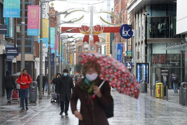 Christmas 2020: A woman wearing a mask to protect herself and others against COVID walks down Henry Street.