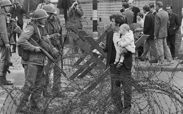 Aug 16, 1969: A civilian with his children confronts soldiers in the streets of Northern Ireland.