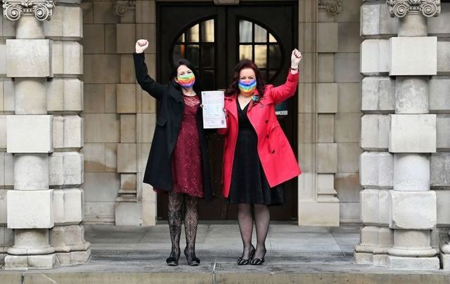 December 7, 2020: Cara McCann (R) and her partner Amanda McGurk (L) hold their marriage certificate aloft as they leave Belfast City Hall in Belfast, Northern Ireland.