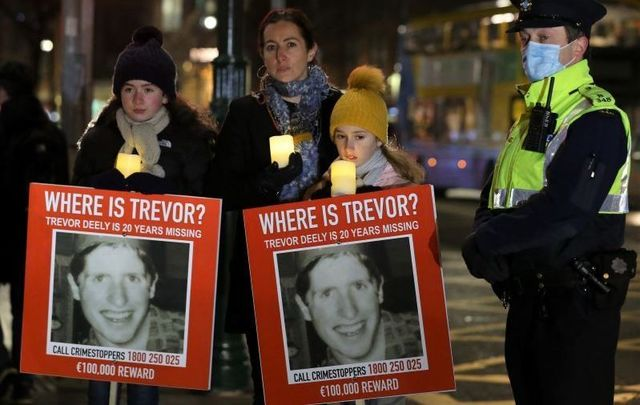 December 7, 2020: Michele Deely with her daughters Lily and Nina and members of the gardai at a vigil for the 20th Anniversary of the Disappearance of Trevor Deely.