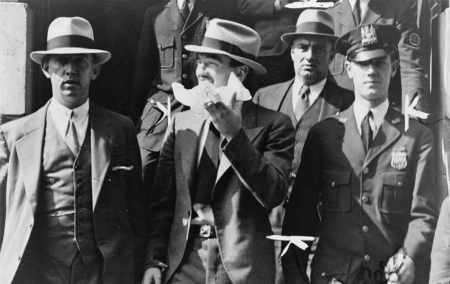 Vincent \'Mad Dog\' Coll, center, leaving a courthouse surrounded by officers.