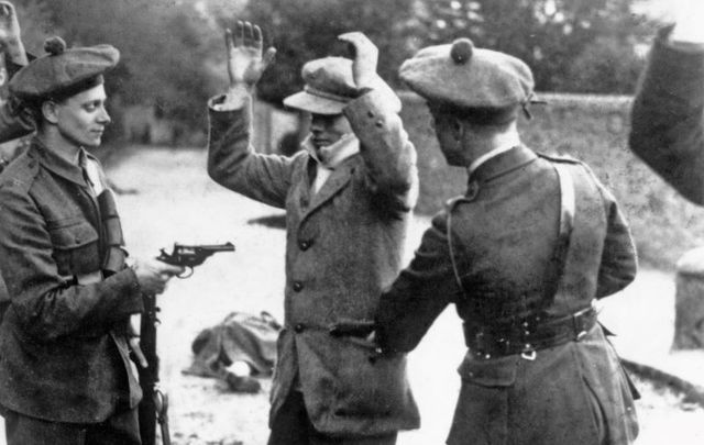 A suspected member of the Irish nationalist party Sinn Fein is searched at gunpoint by temporary constables of the British Black and Tans, during the Irish War of Independence, Ireland, November 1920.
