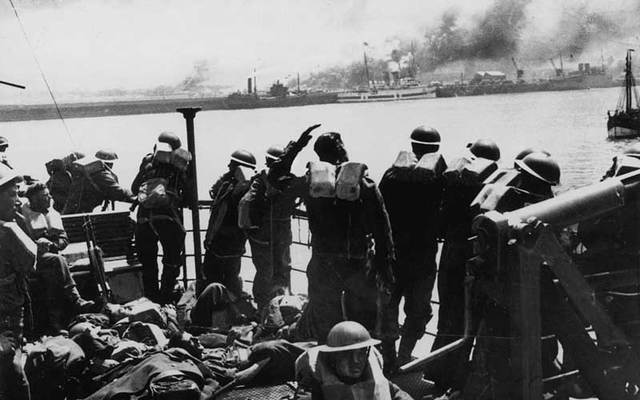 British troops looking back at the French coast from the deck of a steamer on the return to England after the evacuation of Dunkirk, June 1940.