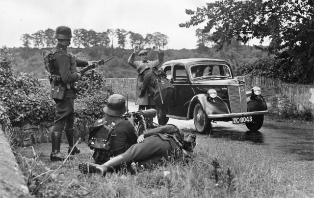 25th July 1939: A driver is searched by armed guards at a military checkpoint on a country road in Ireland during the Second World War.