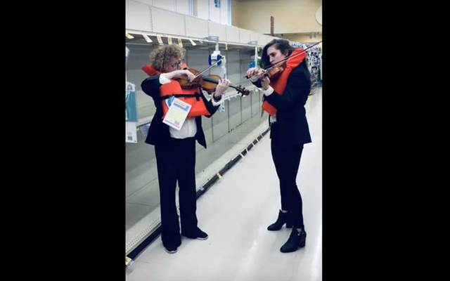 """Violinists Emer Kinsella and Bonnie von Duyke play \""""Nearer My Got To Thee\"""" in the empty toilet paper aisle."""