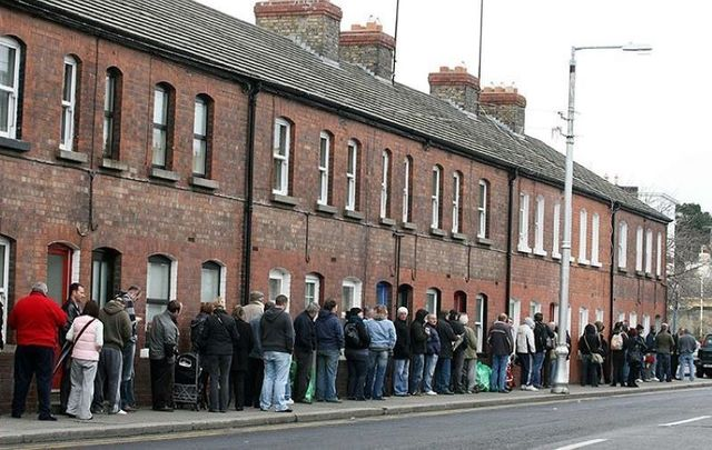 People queue in Dun Laoghaire, Dublin to collect their social welfare payments in 2009.