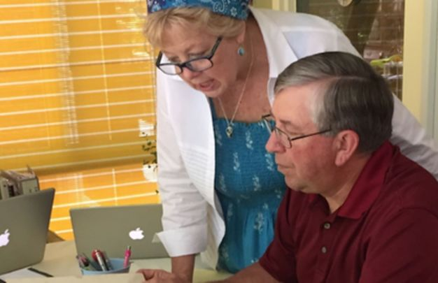 Kate and Mike reviewing family records in the Kennedy family bible passed down through four generations.