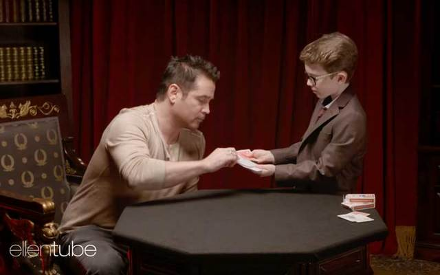 Actor Colin Farrell picks a card for Irish kid magician Aidan McCann.