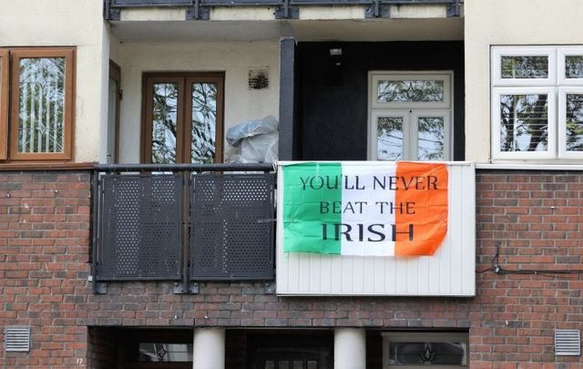"""An Irish flag reading \""""You\'ll never beat the Irish\"""" hanging from the balcony of an apartment on Gardiner Street, Dublin on April 17, 2020."""