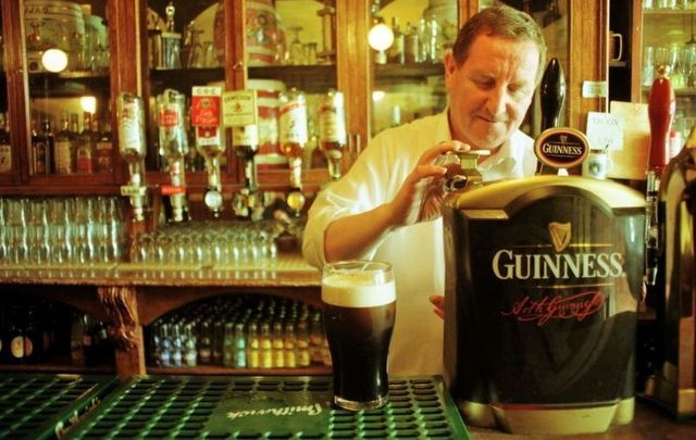 A bartender pulling a pint at Gravediggers pub in Dublin in 1999.
