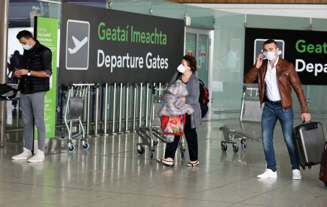 Passengers wearing face masks in an almost deserted Terminal One in Dublin Airport on April 25, 2020.