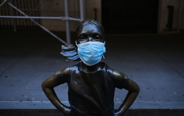 The Fearless Girl, a bronze statue installed for International Women\'s Day, is shown with a surgical mask affixed across from the New York Stock Exchange (NYSE)