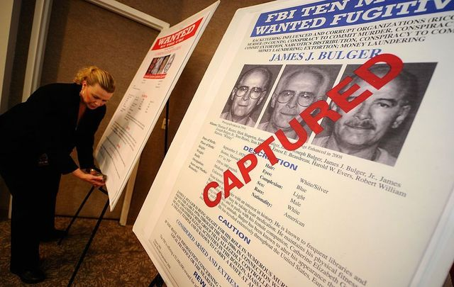 "Mary Prang, Special Agent wit the FBI, adjusts a poster featuring fugitives Boston crime boss James ""Whitey\"" Bulger."