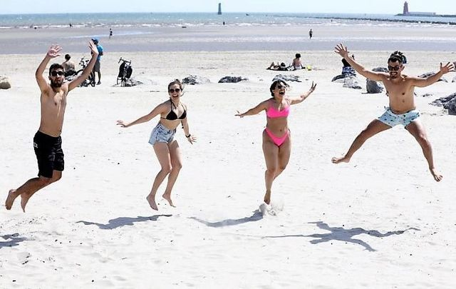 Felipe Chegan from Brazil, Thais Rosa from Brazil, Yasmin Franco from Brazil and Felipe Cardona from Columbia enjoying the good weather and sunshine on Dollymount Strand in Dublin on May 28, 2020.