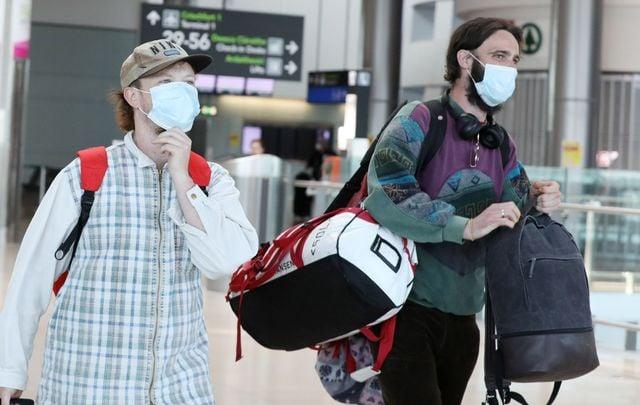 Passengers wearing masks walk through Dublin Airport.