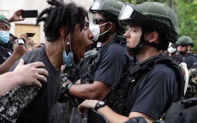 A protestor shouts at a law enforcement officer during a protest in Washington DC.