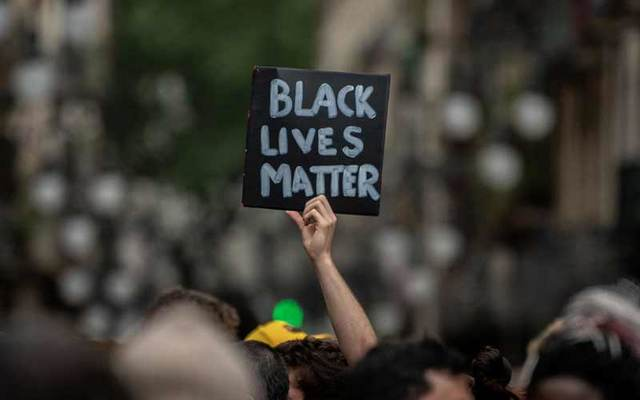 "A protester holds up a ""Black Lives Matter\"" sign."