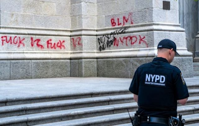 May 30, 2020: An NYPD officer walks by a vandalized St. Patrick\'s Cathedral in New York City.