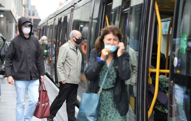 People wearing masks as they board and disembark the Luas in Dublin\'s City Center on July 4, 2020.