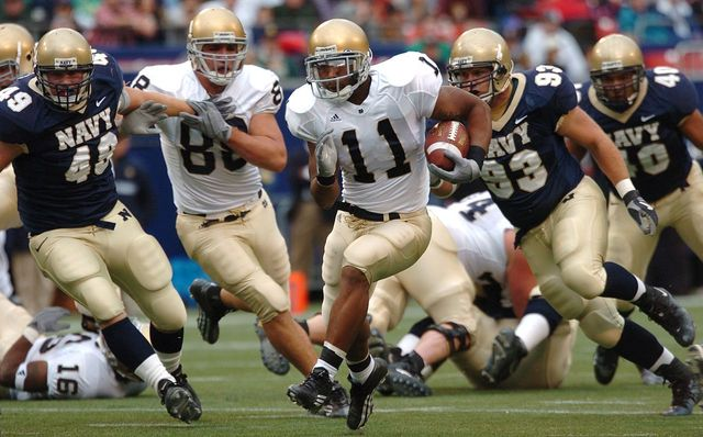 Notre Dame running back Marcus Wilson races for yardage as a trio of U.S. Naval Academy Midshipmen defenders gives chase at Giants Stadium in East Rutherford, N.J, in Oct 2004.
