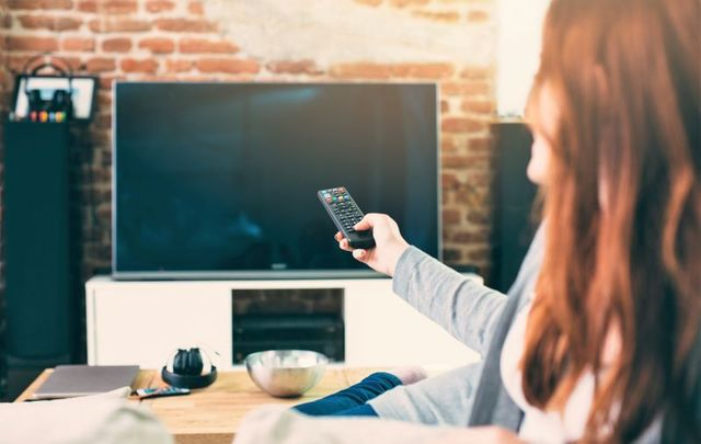 Woman pointing remote at television.