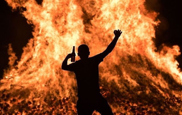 A young loyalist man is seen dancing at the Ballycraigy estate 11th night bonfire on July 11, 2020 in Antrim, Northern Ireland.