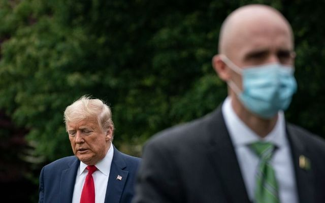 A secret service agent dons a mask while Donald Trump remains maskless. The President has said that he will not order Americans to wear facemasks.