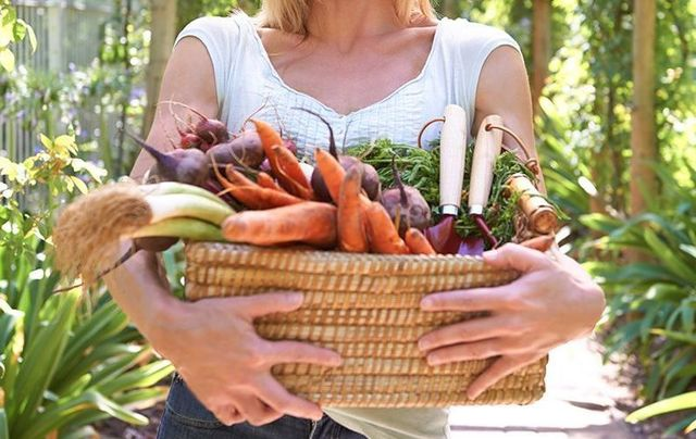 A woman holding a basket of vegetables.
