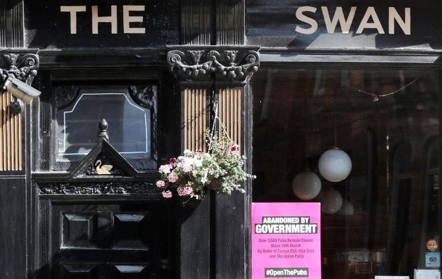"September 15, 2020: The Swan bar in Dublin with a sign outside that reads ""Abandoned by Government\"" and \""#OpenThePubs\"""