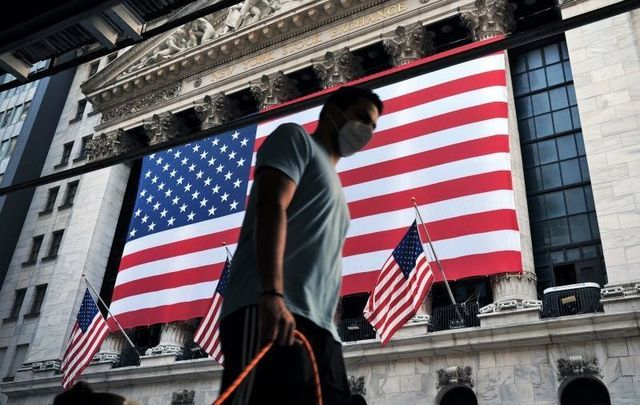September 11, 2020: A man wearing a face mask walks by the New York Stock Exchange in New York City.