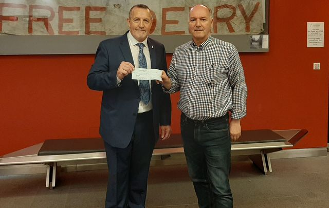 Malachy McAllister presents a check to Tony Doherty at the Museum of Free Derry.
