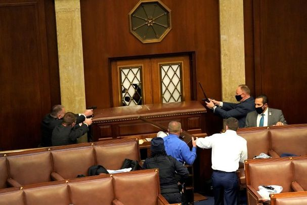 January 6, 2021: Law enforcement officers point their guns at a door that was vandalized in the House Chamber during a joint session of Congress in Washington, DC.