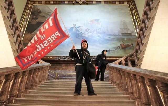 January 6, 2021: A pro-Trump rioter holds a Trump flag inside the US Capitol Building near the Senate Chamber in Washington, DC.