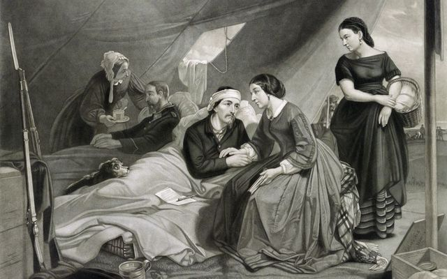 Women attend to wounded soldiers in a hospital tent during the Civil War in this vintage illustration.